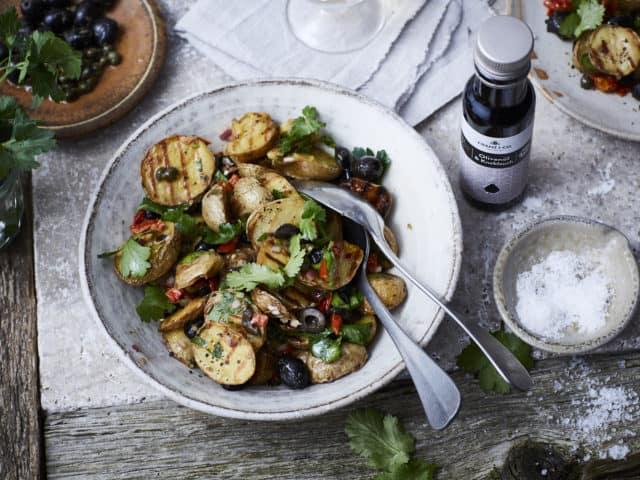 Bratkartoffelsalat mit dem Würzöl Olive & Knoblauch von FRANZ & CO. auf einem Teller.