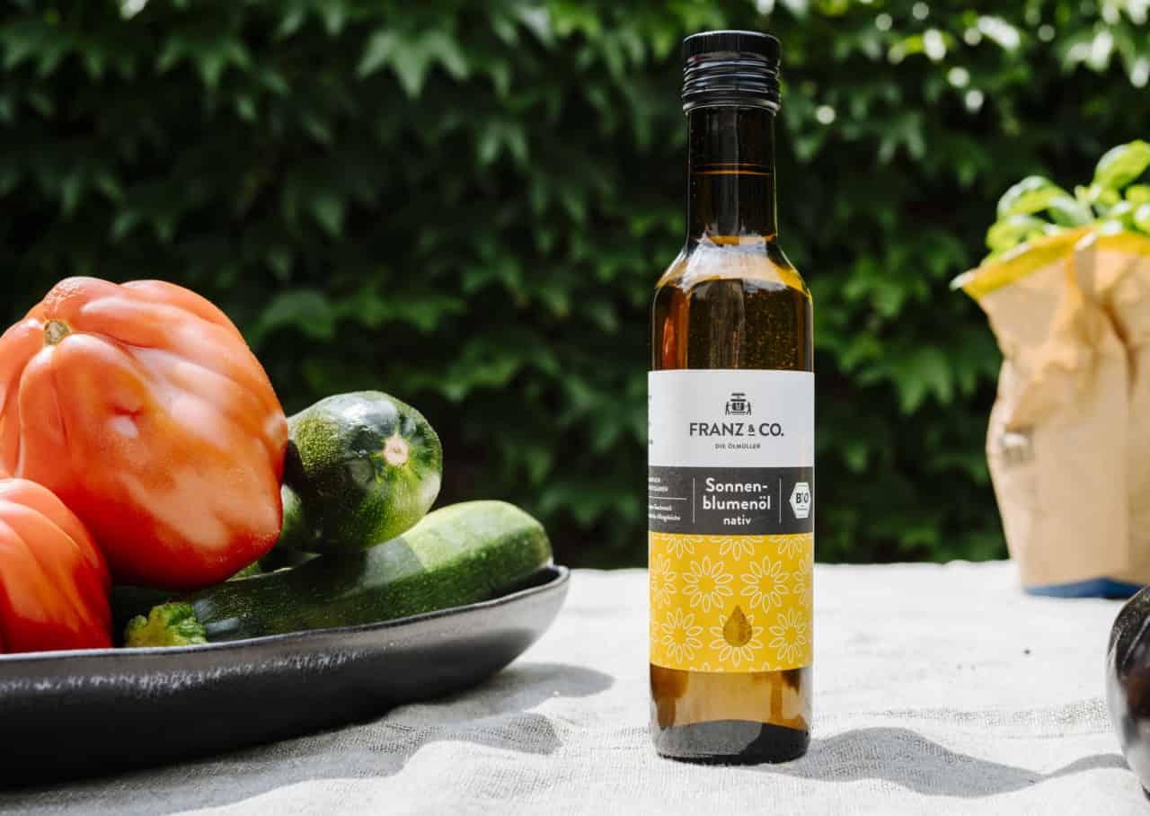 Das FRANZ & Co. Sonnenblumenöl steht auf dem Tisch zwischen Zutaten