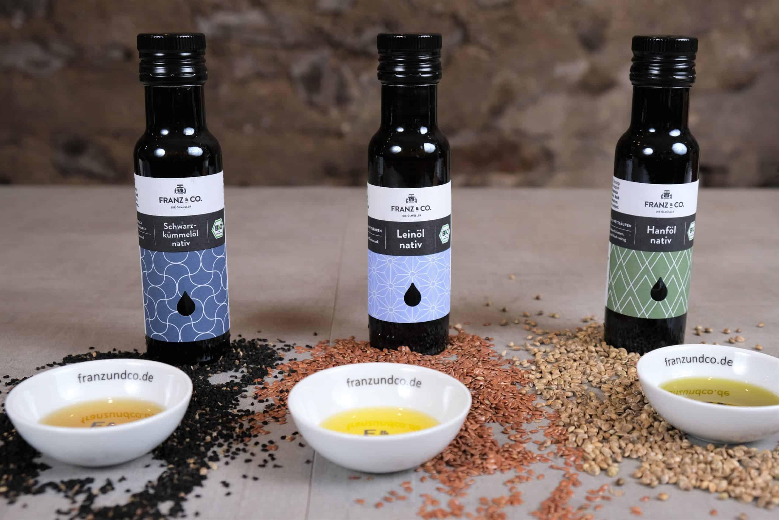 Drei Vitalöle Schwarzkümmelöl, Leinöl und Hanföl mit der Saat und und dem Öl im Schälchen